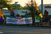 """Protesters held up a sign that said """"Make a Moral Stand against Farmworker Poverty & Abuse"""" for passing cars to read."""
